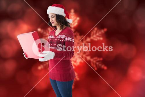 Composite image of festive brunette in winter clothes opening gift