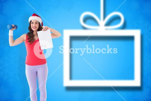 Composite image of festive athletic brunette holding page and dumbbell