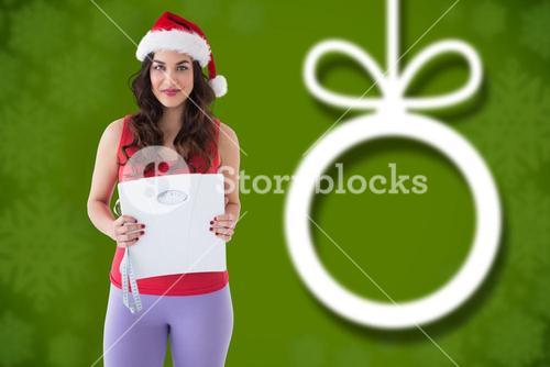 Composite image of festive fit brunette holding page and measuring tape