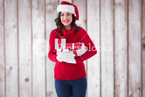 Composite image of festive brunette in winter clothes holding gifts
