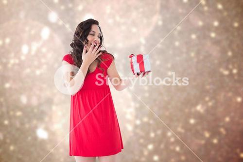 Composite image of astonished brunette holding a gift