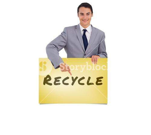 Composite image of goodlooking man holding and pointing at a big poster