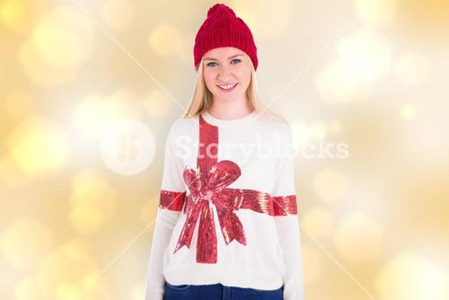 Composite image of festive blonde in christmas jumper