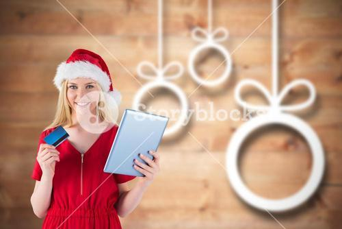 Composite image of festive blonde shopping online with tablet