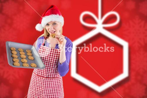 Composite image of festive blonde showing hot cookies