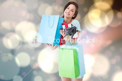 Composite image of happy brunette with shopping bags and gifts