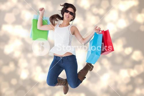 Composite image of happy brunette jumping with shopping bags