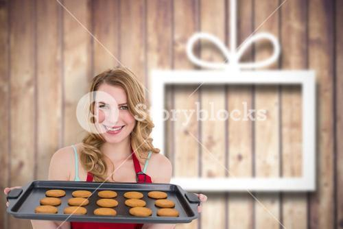Composite image of smiling woman showing hot cookies