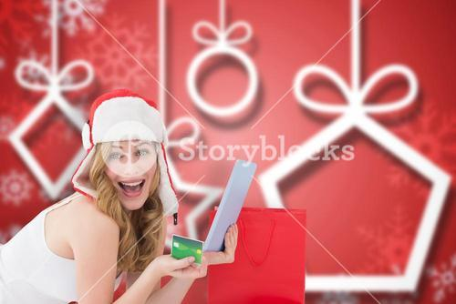 Composite image of woman holding a credit card surrounded with gifts