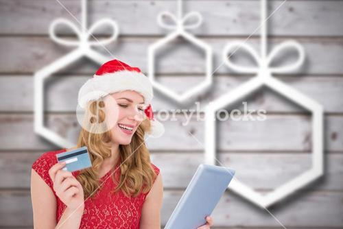 Composite image of festive blonde woman using her credit card and tablet pc