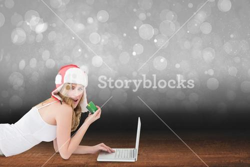 Composite image of happy woman shopping online lying on the floor