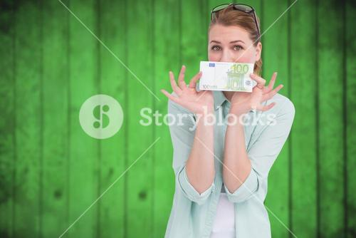 Composite image of pretty woman showing an one hundred euro note