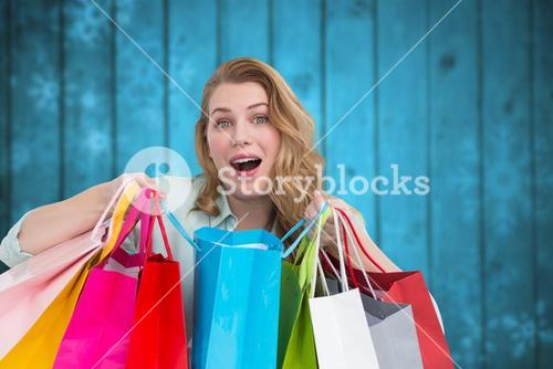 Composite image of overwhelmed young woman with shopping bags
