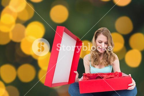 Composite image of pretty woman opening a gift smiling at it
