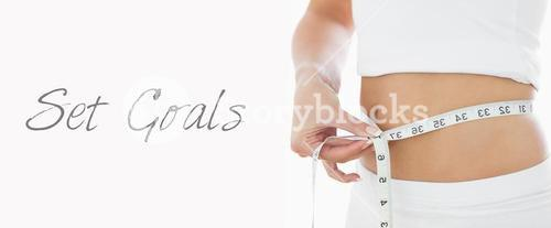 Closeup midsection of woman measuring waist
