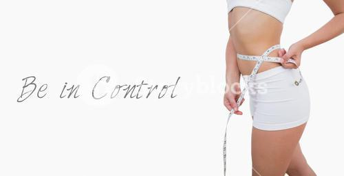 Midsection of fit woman measuring waist