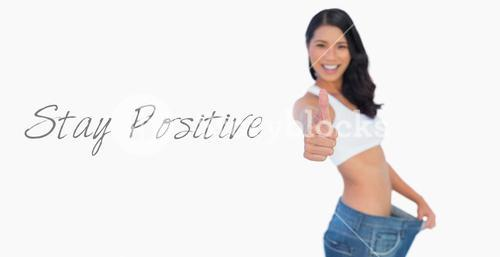 Victorious woman holding her too big pants thumbs up