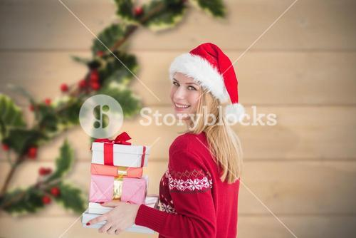 Composite image of woman holding christmas presents