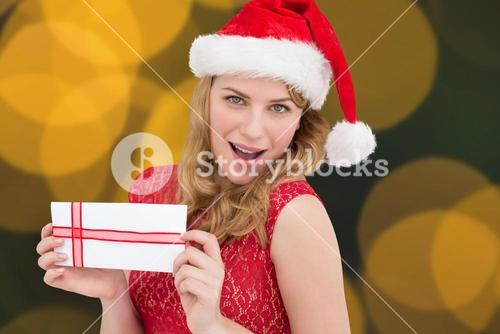 Composite image of woman smiling with present in hands