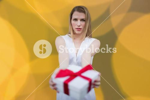 Composite image of woman offering a present