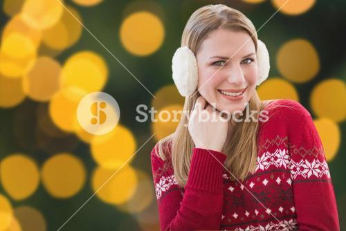 Composite image of woman wearing warm ear muffs