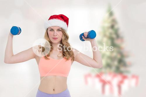 Composite image of festive fit blonde holding dumbbells