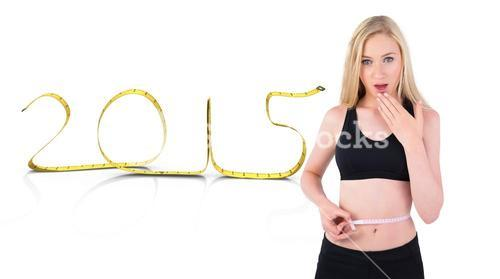 Composite image of fit young blonde looking at measuring tape