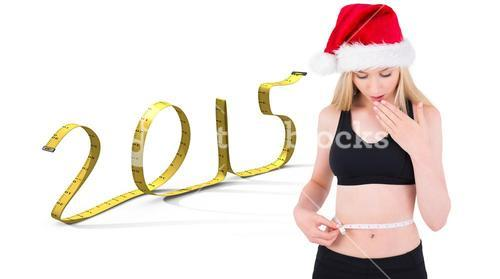 Composite image of fit festive young blonde looking at measuring tape
