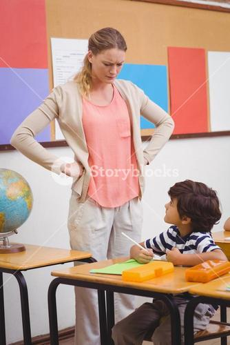 Angry teacher looking pupil with hands on hips