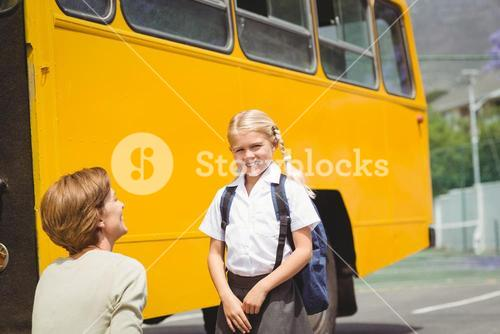 Mother with her daughter by school bus