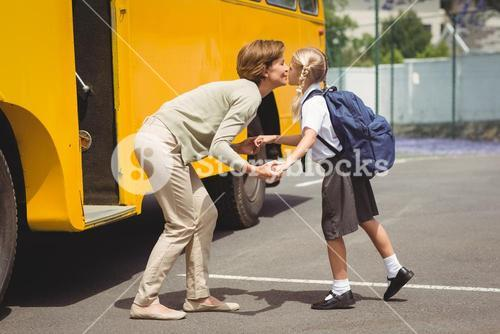 Mother kissing her daughter by school bus