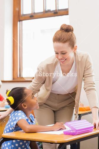 Teacher and pupil working at desk together