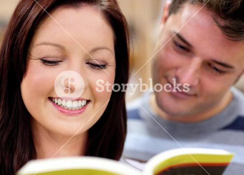 Close up of a smiling couple of students reading a book