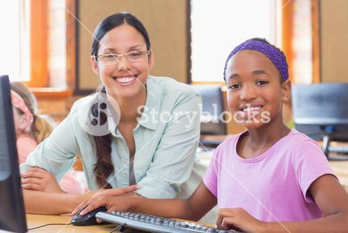 Cute pupil in computer class with teacher
