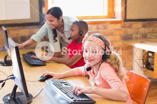 Cute pupils in computer class with teacher