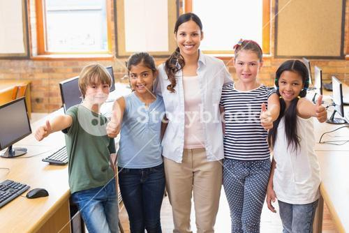 Cute pupils and teacher smiling at camera in computer class