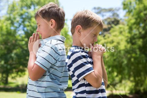 Little boys praying in the park
