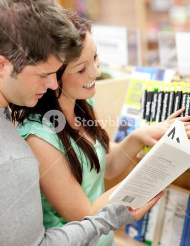 Beautiful couple of students reading a book