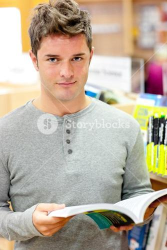 Serious young man reading a book