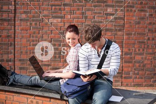 Two students working together with book and laptop outside