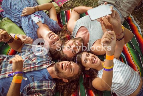 Happy hipsters lying on the grass