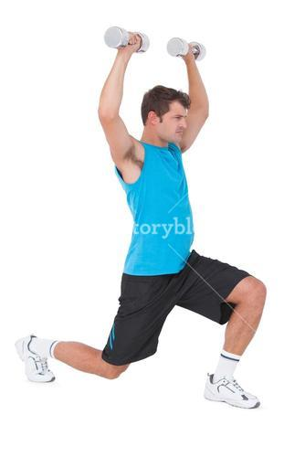 Fit man lifting dumbbells while lunging