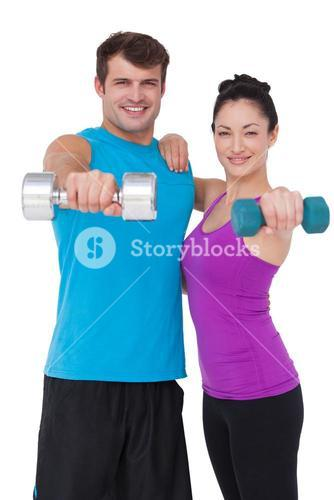 Fit man and woman lifting dumbbells