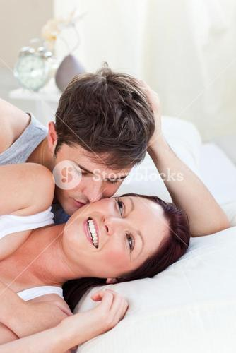 Affectionate couple lying on bed in the bedroom