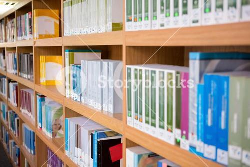 Volumes of books on bookshelf in library