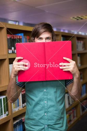 Student covering face with book in library