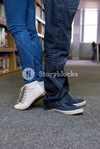 Students standing back-to-back in the library
