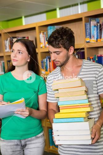 Students with pile of books in the library