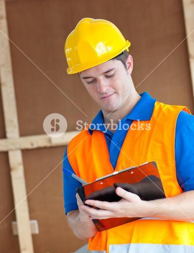 Handsome worker with hardhat taking notes on his clipboard
