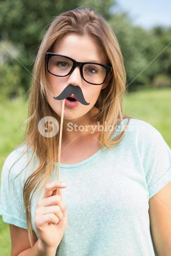 Pretty blonde smiling at camera with fake mustache